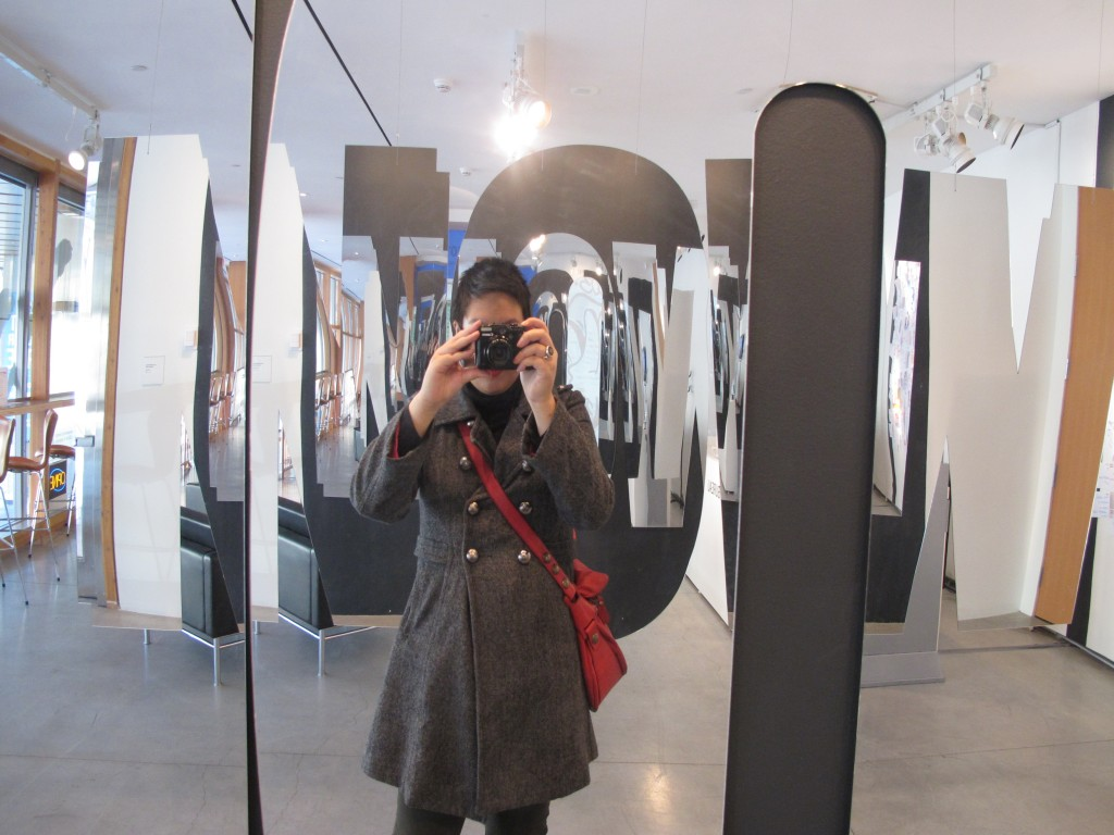 Infinite NOW (2012) is a work that is completed by visitors to the gallery space.  Mirrored NOW sculptures frame the viewer and reflect their image, a visual remark on the role of the viewer as both creator and member of the masses.  Courtesy of the Art Gallery of Ontario.  Photograph taken by the author.